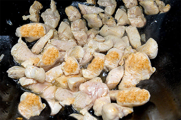 A close up of a wok with chicken bring browned and stir fried