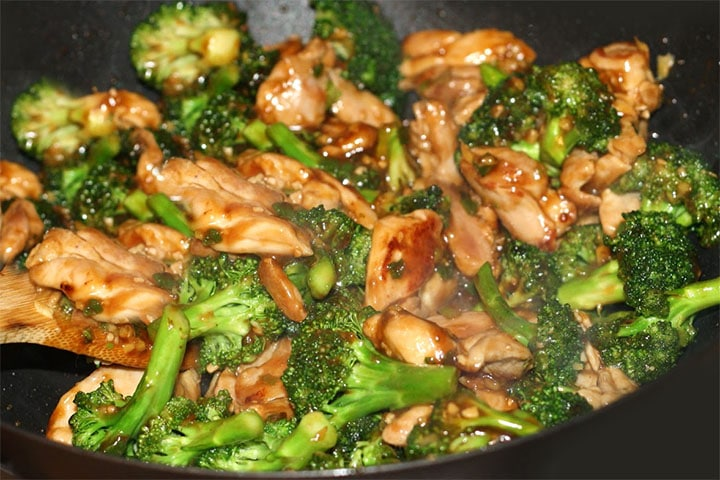 A close up of the chicken with broccoli being stir fried with the sauce in the wok