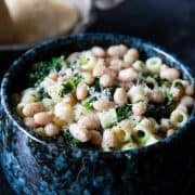 a close up of a bowl of white bean soup piled high with pasta and spinach