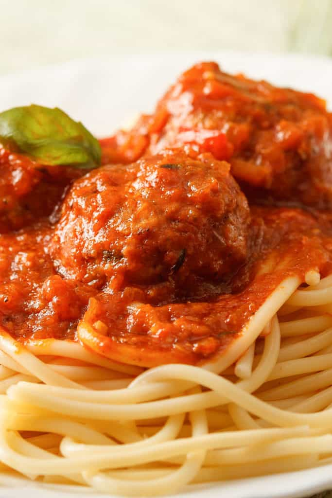 A close up of meatballs in sauce on spaghetti