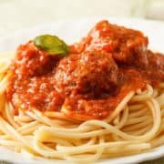 Italian Sausage Meatballs & Spaghetti & Pasta on a plate garnished with herbs