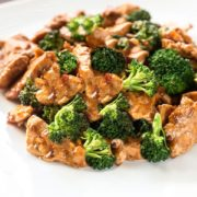 A close up of a white dish with the Chinese Chicken & Broccoli covered in a deep golden sauce.
