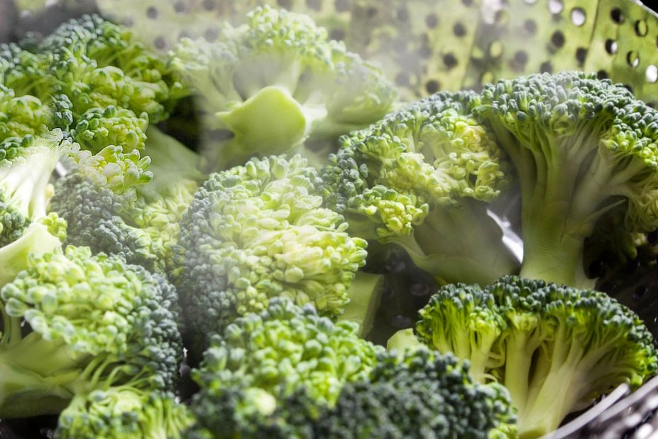 A close up of broccoli cooking in s steamer surrounded by steam