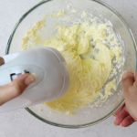 The buttercream being mixed with an electric mixer