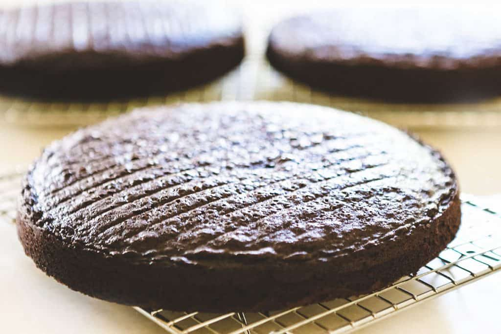 three chocolate cakes cooling on cooling racks