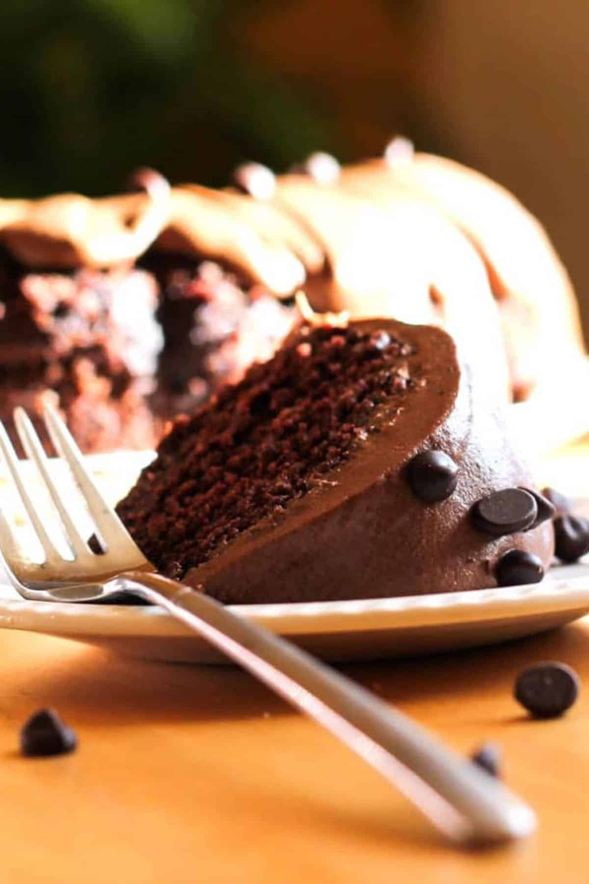 a slice of Chocolate Chip Cake with Chocolate Butter Cream Icing on a plate with a fork
