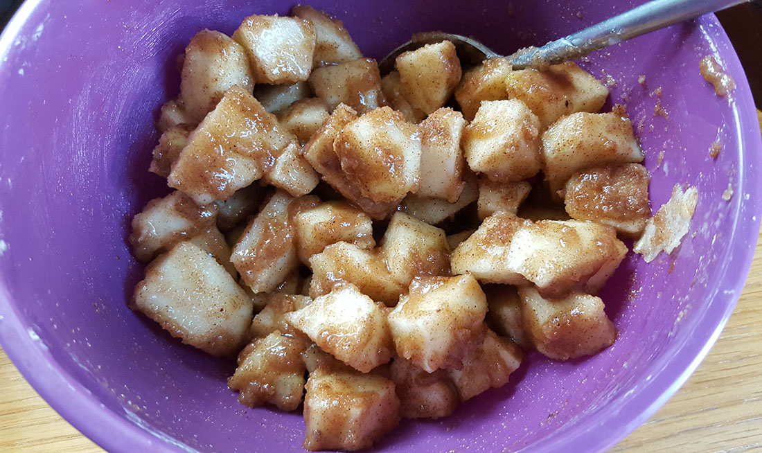 A mixing bowl with chunks of apples coated in a thick sugary coating