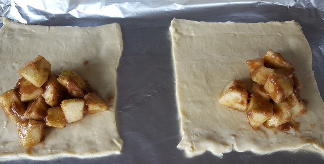 squares of pastry with a pile of apple filling on half of the square
