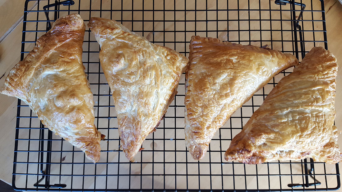 Apple Turnovers that are crisp and golden brown cooling on a wire rack