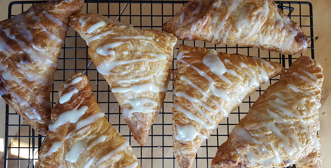 Apple turnovers on a cooling rack drizzled with icing