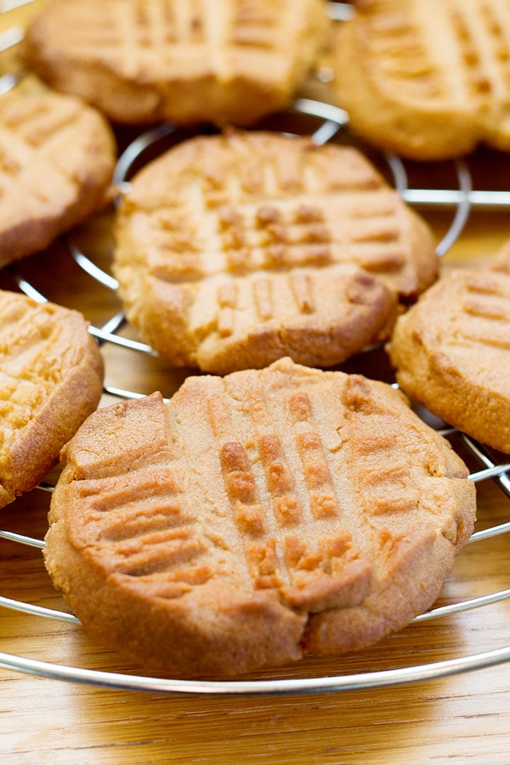 A cooling rack filled with fresh baked Classic Peanut Butter Cookies with golden edges and crisscross pattern