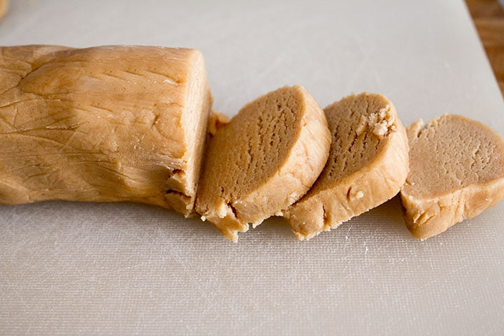 The chilled dough shaped into a log shape with three slices cut out of it