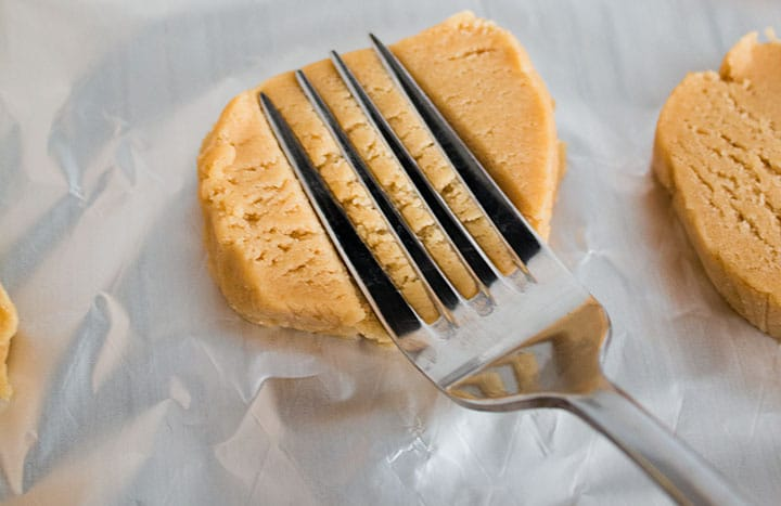 A sliced disc of dough with a fork making indents into it