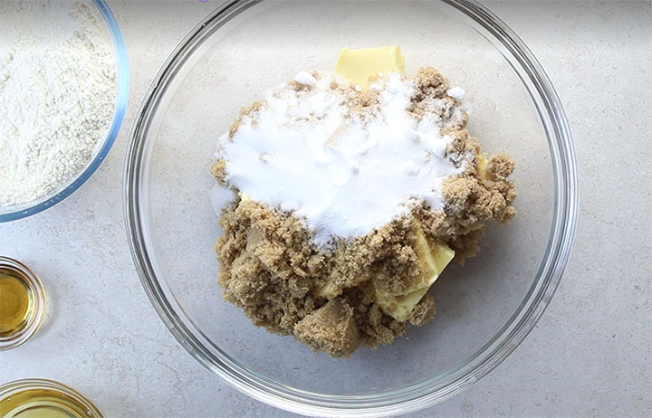 The butter and sugars in a glass mixing bowl