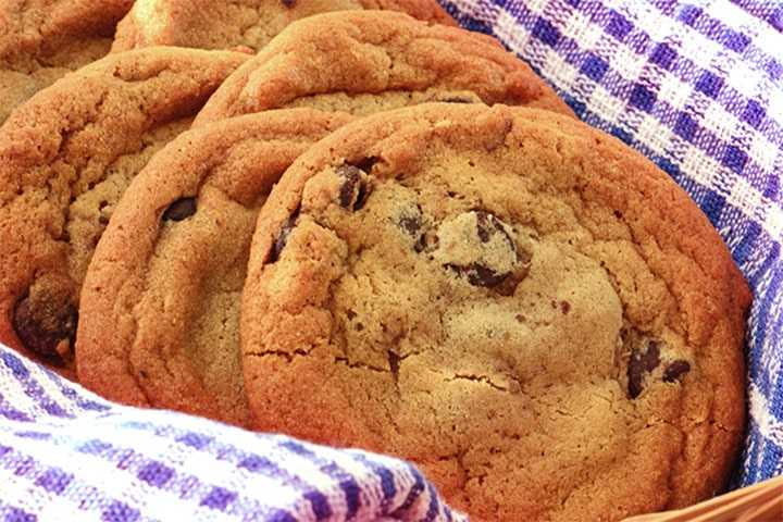 A basket of classic chocolate chip cookies in a basket lined with a cloth napkin
