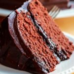 A close up of a slice of devils food cake with chocolate icing
