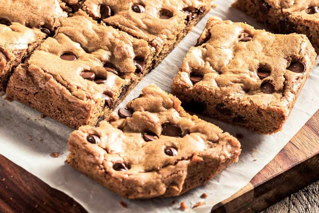 a close up of chocolate chip blondies cut into squares