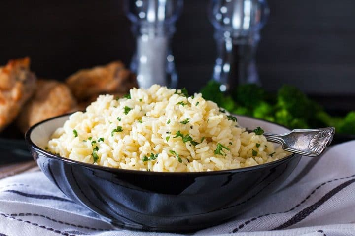 A serving bowl filled with Rice Pilaf sprinkled with chopped parsley.