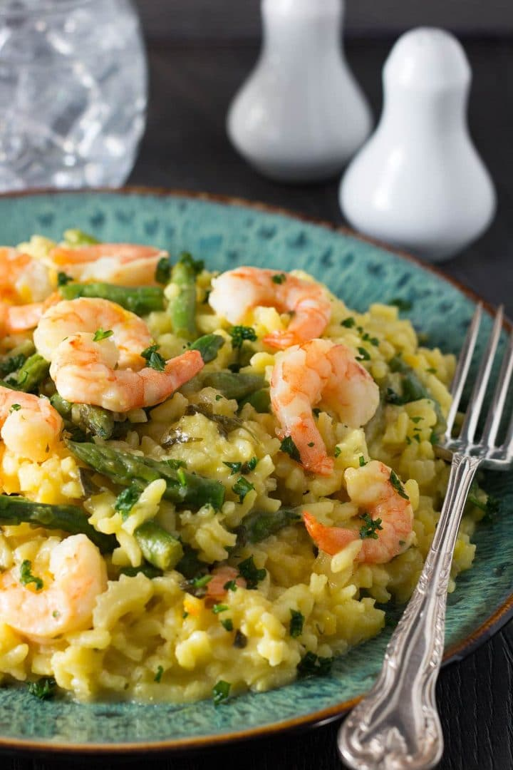 Shrimp and Asparagus Saffron Risotto on a plate sprinkled with chopped parsley and a fork laying near the plate