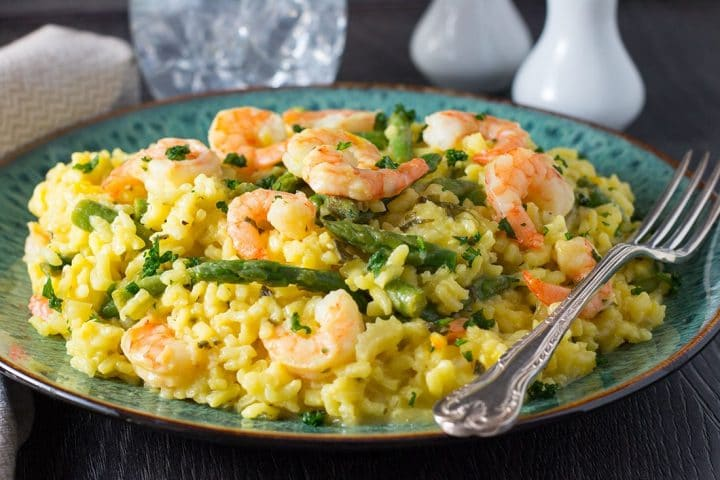 Shrimp and Asparagus Saffron Risotto  served on a plate with a fork laying next to it