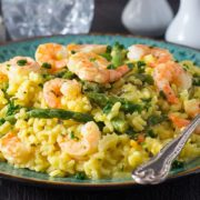 A dish of shrimp and asparagus saffron risotto with a fork