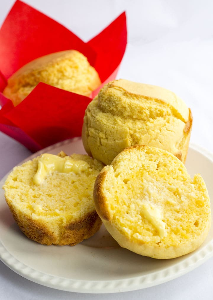 A warm corn muffin on a plate with butter melting into it