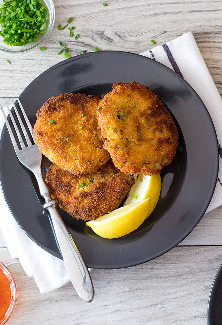 Three Crab Cakes on a plate with lemon wedges and a fork next to it