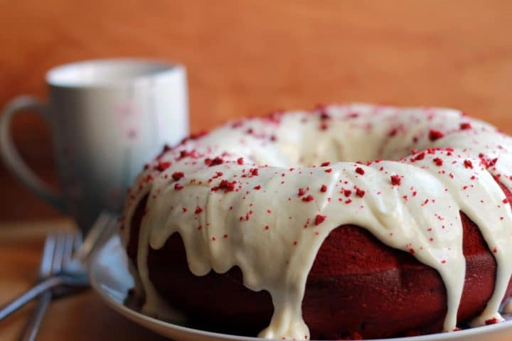 A close up of the Red Velvet Bundt Cake with Cream Cheese Icing scattered with the red crumbs as decoration.