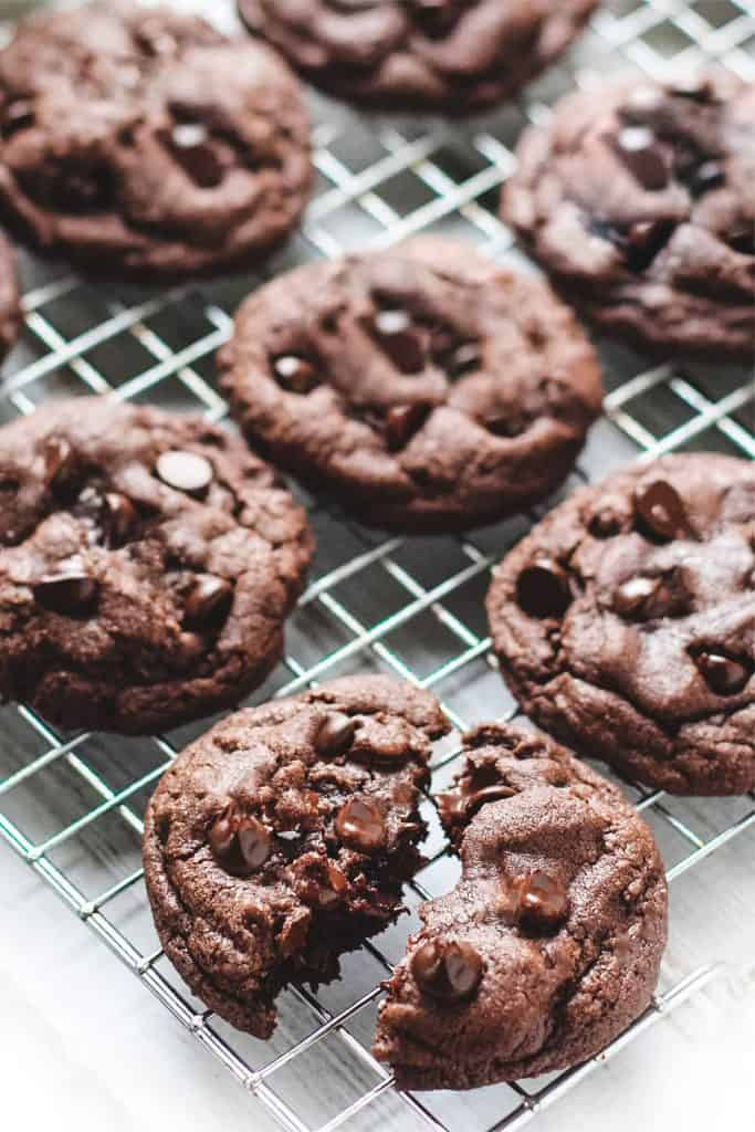 Double Chocolate Chip Cookies on a cooling rack with one broken open to show gooey chocolate chips