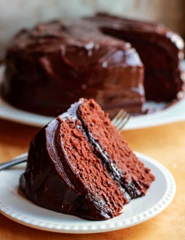 A slice of devils food cake with the cake in the background