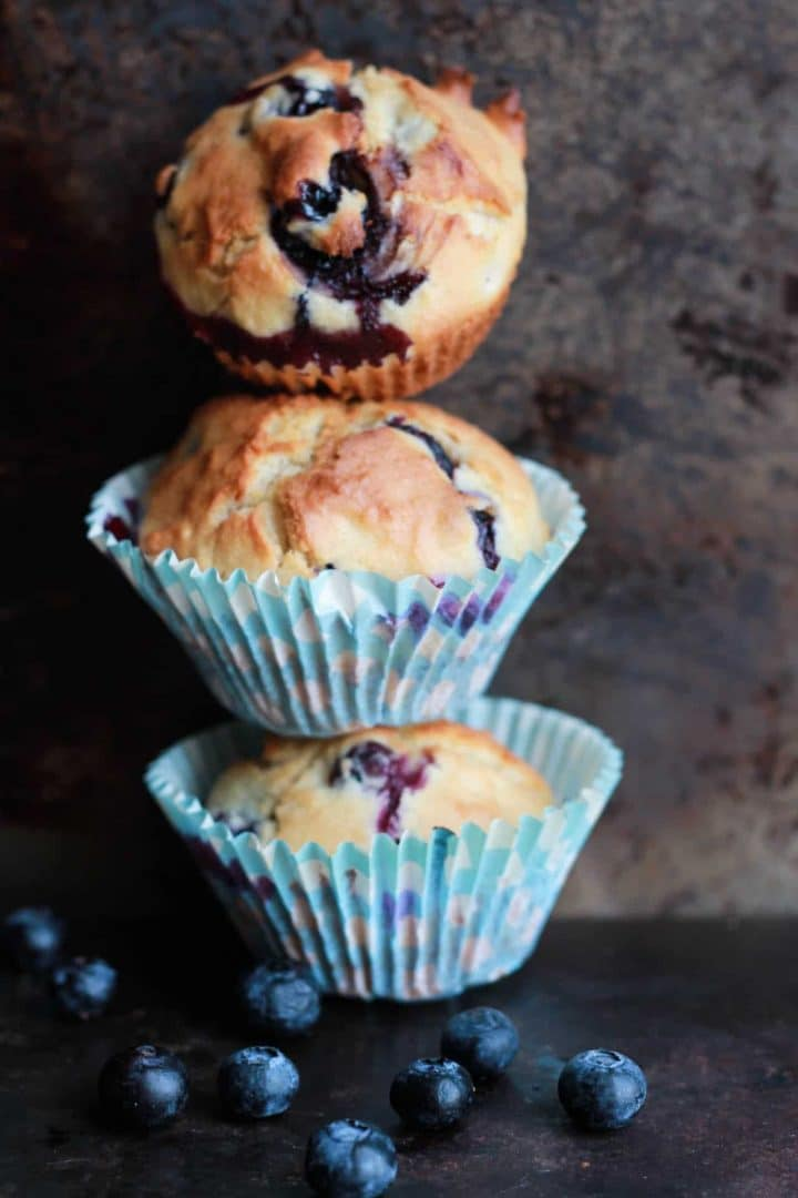 Three Blueberry Scone Muffins in blue muffin wrappers piled on top of each other