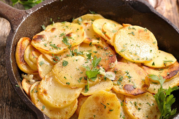Crispy Garlic Roasted Potatoes in the pan with parsley scattered over it