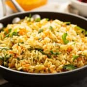 Vegetarian Rice Pilaf in a pan with dishes of vegetables in the background