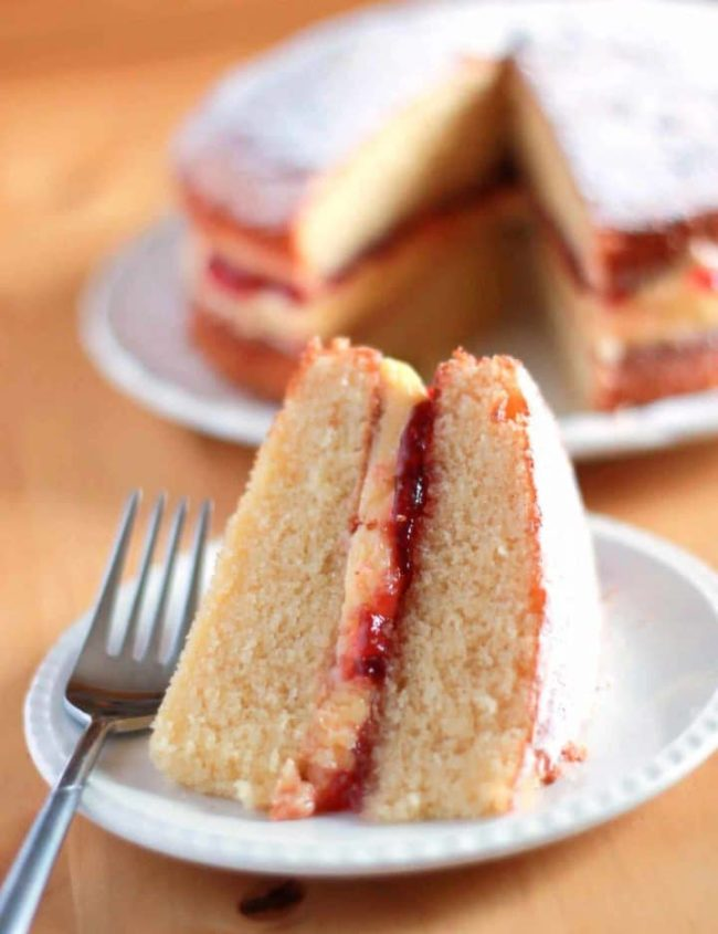 Slice of Victoria Sponge Cake layered with buttercream icing and raspberry jam