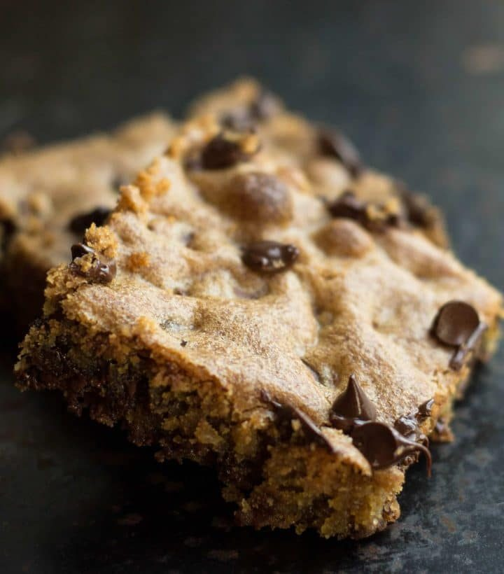Two slices of Classic Chocolate Chip Blondies still warm with melted chocolate chips
