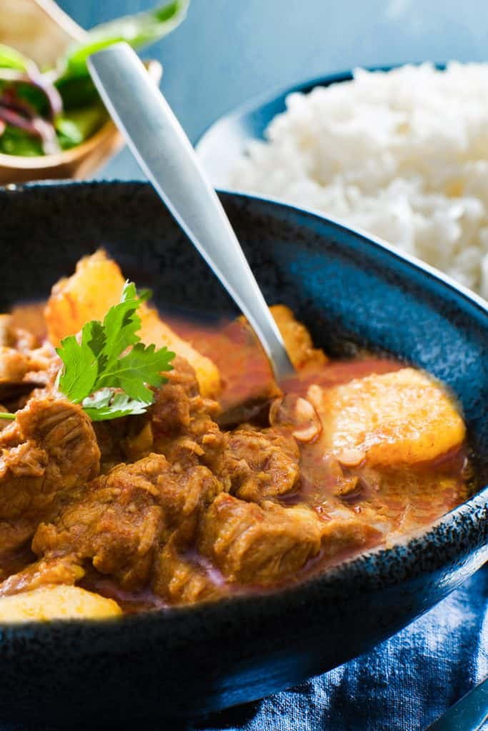 A dish of massaman curry with a bowl of white rice in the background