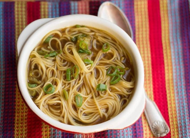 Quick & Easy Chinese Noodle Soup in a bowl, scattered with green onions with a spoon next to it