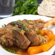 Slow cooked lamb shanks served with carrots on a plate