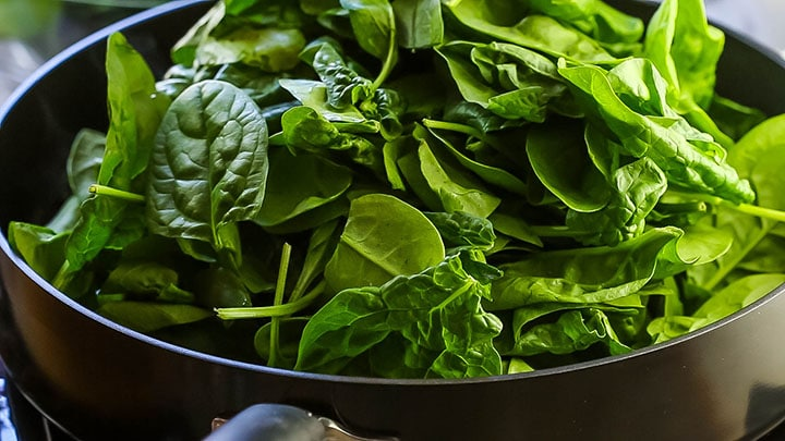 Spinach piled high in a pan.