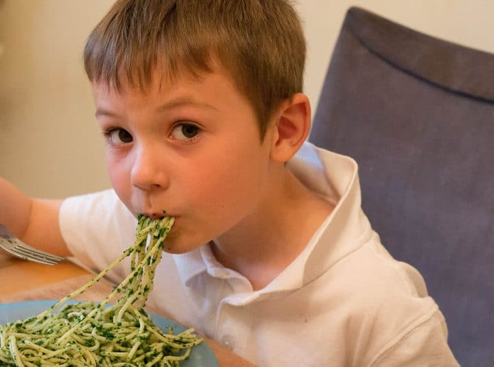 A little boy eating a dish of Spaghetti with Spinach Sauce with strands of spaghetti hanging from his mouth