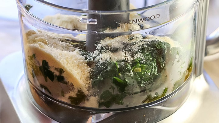 The spinach and garlic added to a food processor with grated cheese and pasta water