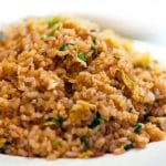 A close up of golden fried rice showing the freen onions and egg throughout