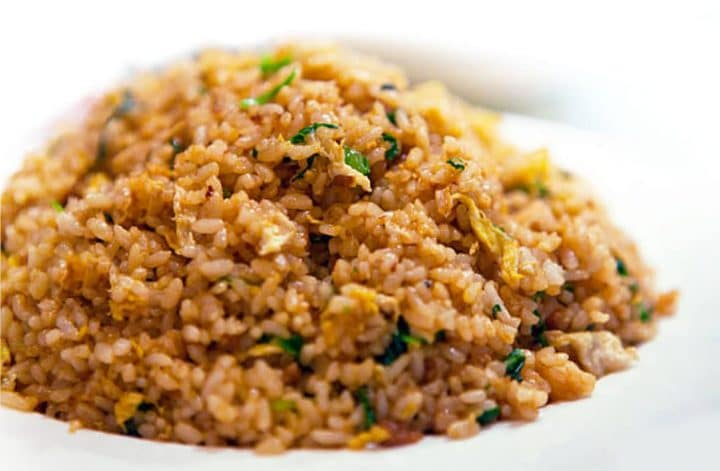 A close up of golden fried rice showing the freen onions and egg throughout.