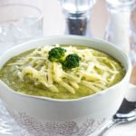a Bowl full of Healthy creamy broccoli soup with shredded cheese and broccoli on top