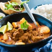 A dish of massaman curry with a bowl of white rice and limes in the background