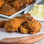 Three pieces of Easy Oven Fried Chicken speckled with parsley