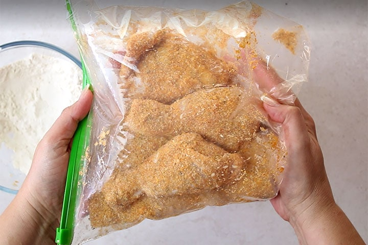 Three pieces of chicken being coated with bread crumbs in a plastic bag.