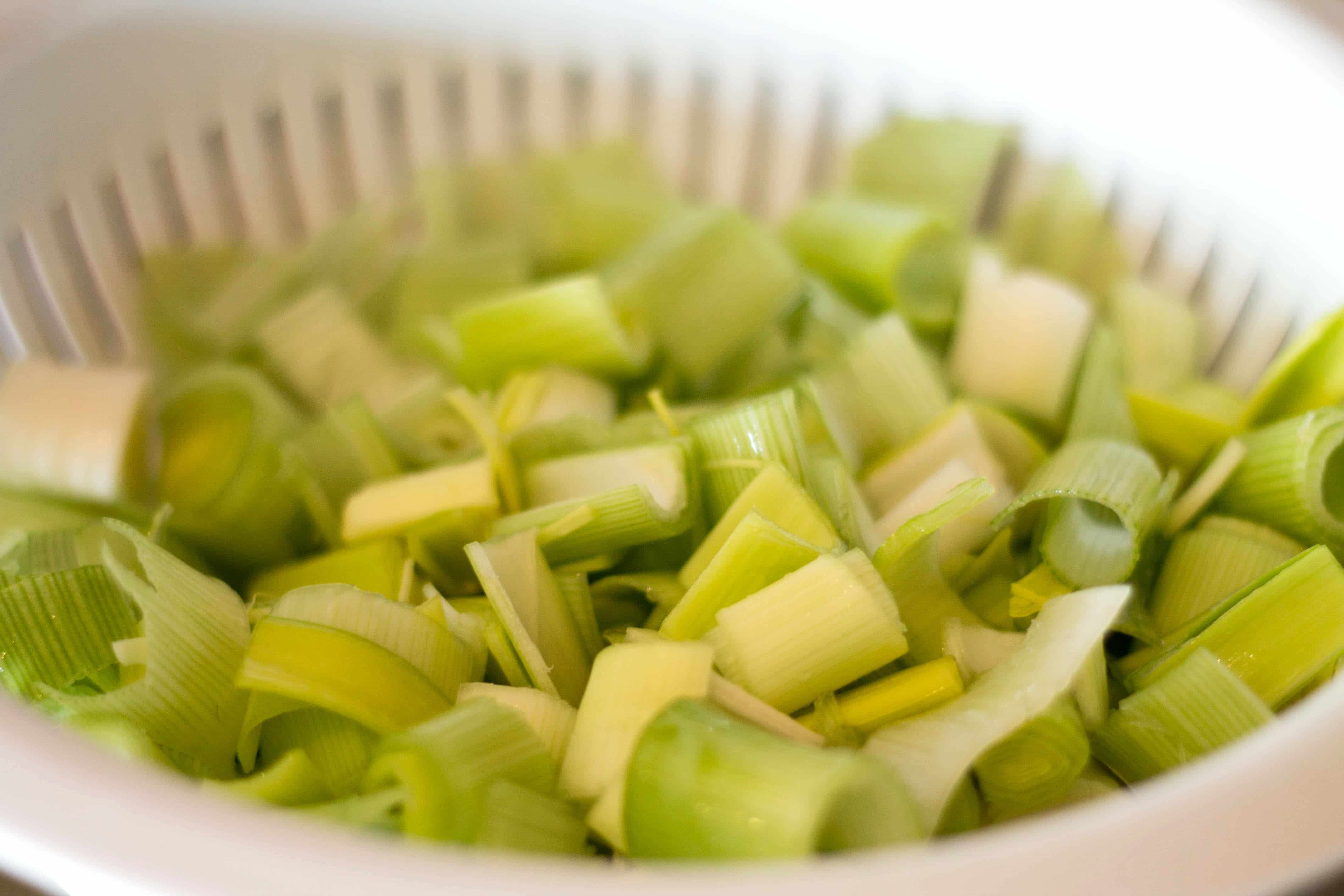 sliced and washed leek draining in a colander