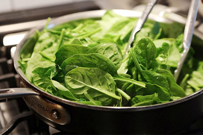 Spinach in a pan being stirred with tongs