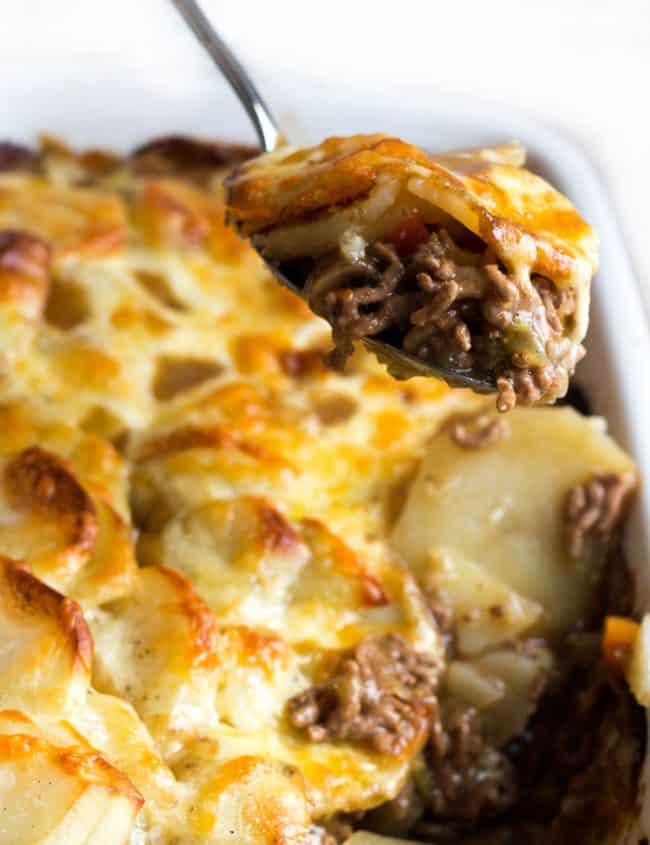a spoon serving cottage pie stopped with cheesy potatoes